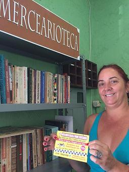 Mulher ao lado da estante de livros da Mercearioteca