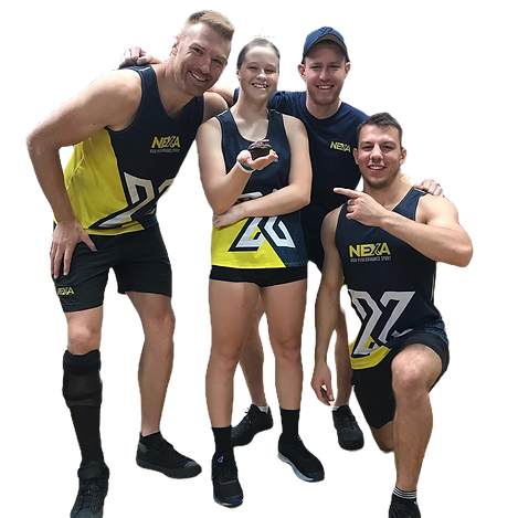 Coach Dan, Coach Ben and Coach Sean with vision impaired para athlete, Courtney holding a chocolate cupcake. They are huddled together and smiling at the camera wearing the NEXA singlet, yellow and blue with a big white X on the front.
