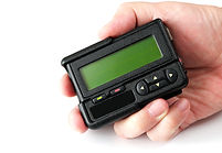 Old black pager in hand isolated on whit