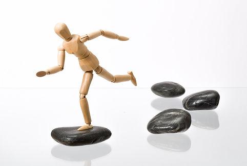 Holzmännchen springt über Steine