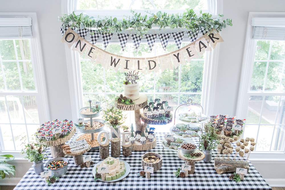 Party Food Table - One Wild Year Monthly Photo Board 1st Birthday - Wild One Smash Cake Photo Session - One Wild Year - Boy's 1st Birthday Party - Ideas, inspiration, decor, party food and menu, kids activities and games, cake smash photo session, bear theme, wild one wilderness tree teepee outdoor theme, decorations, cake, cookies, and more!
