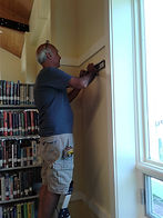 Friend of OCAC Rich Frazino installs art hanging system at the Oxford Public Library