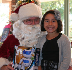 Santa delivers a toy robot to a very happy young lady