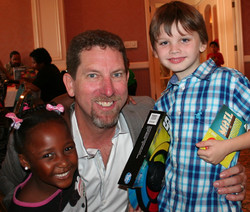 Event organizer Troy Davis has his picture taken with two happy children, photo credit goes to one o