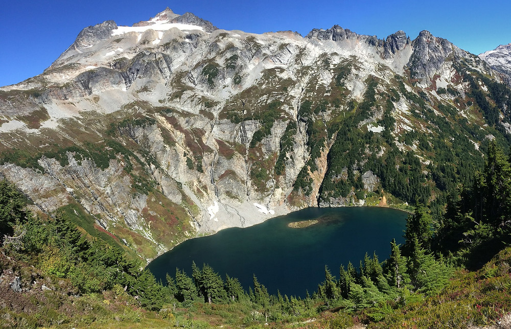 A panorama of Doubtful Lake in the North Cascades, surrounded by meadows of fall colored berry bushes, western hemlock, and the Sahale Arm trickling waterfalls from the glacier.