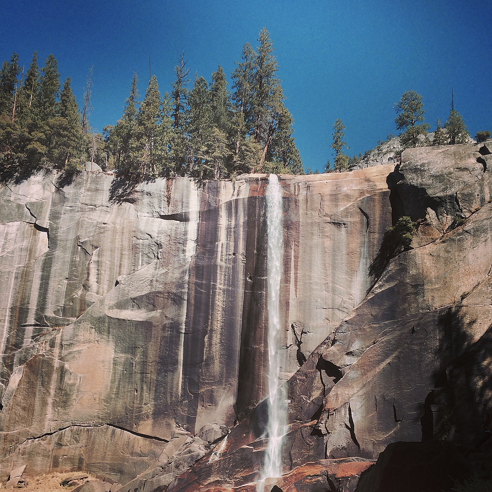 A photo of Vernal Falls in summer, small compared to the colorful granite cliff it shoots over.