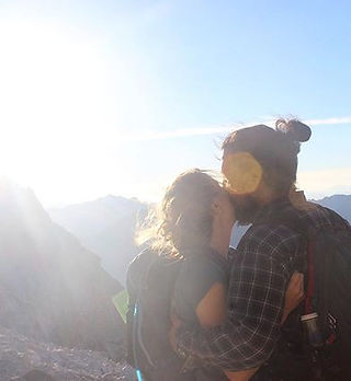 A photo of a couple kissing on a mountaintop.