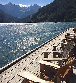 A photo of the Ross Lake Resort dock empty with Colonial Peak in the background, on a sunny day.
