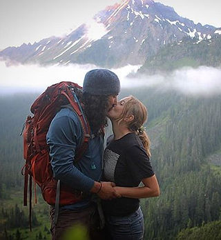 A photo of a hiker couple kissing in front of a mountain, Mount Larrabee in the Mount Baker - Snoqualmie National Forest.