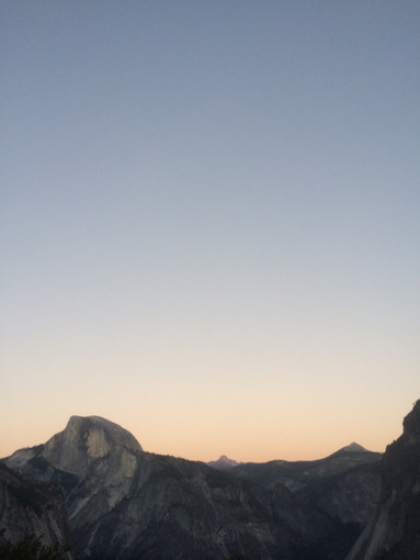 A photo taken at sunset, looking across at Half Dome and the corner of Glacier Point.
