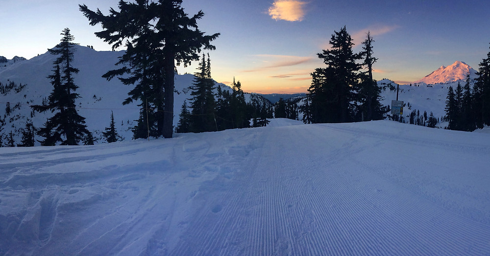 A photo taken from the top of the Blueberry Cat Track at the Mount Baker Ski Area, of a pink and orange sunrise coming up on the eastern side of Mount Baker and the western side of Mount Shuksan still dark.