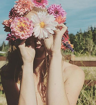 A photo of a girl with dahlias in her hair and held over her eyes.