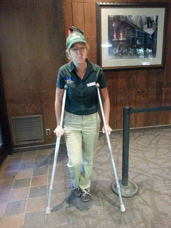 A photo of me in my work uniform, making a sad face and holding myself on crutches.