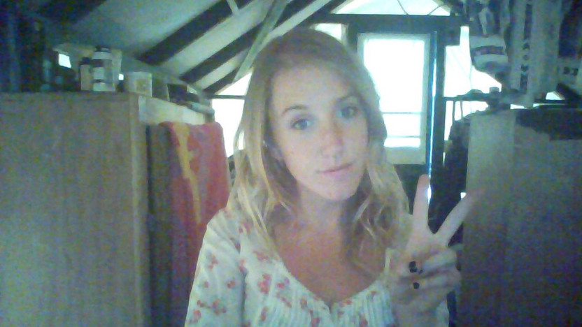 A photo of me giving the camera a peace sign, happy in my tent-cabin.