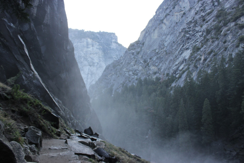 A photo of a narrow rock path, surrounded by high cliffs on all sides and mist rising from the gorge below.
