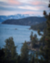 A photo of the trees along the shore of southeastern Lake Tahoe facing north at sunset.