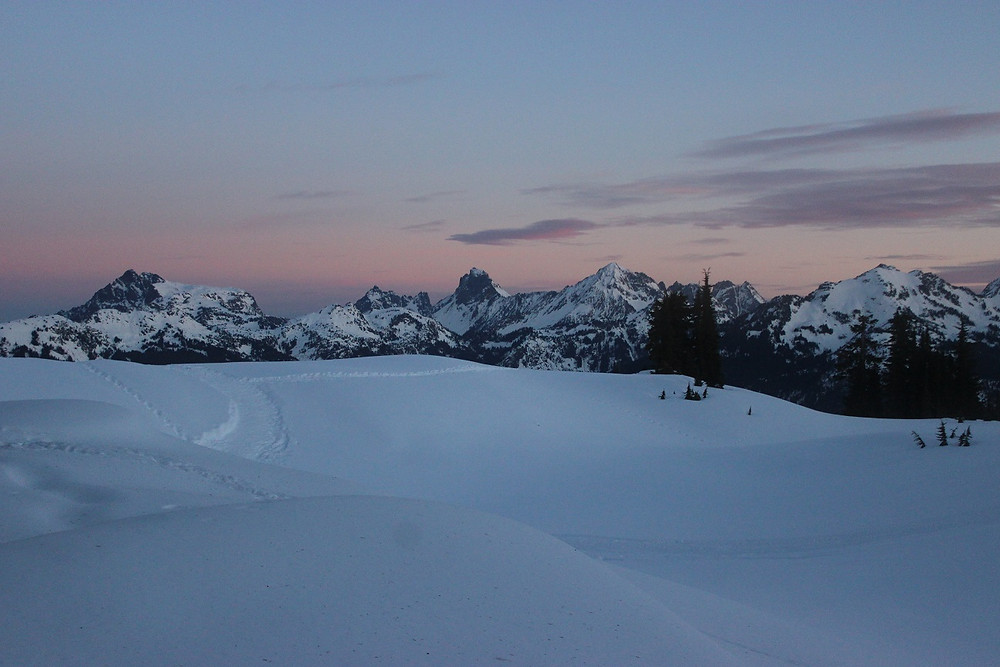 A photograph of untouched powder and the peaks of the Nooksack Range in the distance, against the pink sunrise.