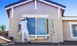 house painting professional working on exterior of home