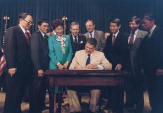 Ronald_Reagan_signing_Japanese_reparatio
