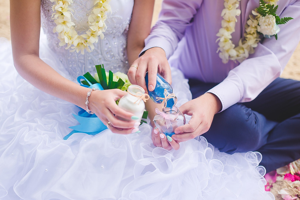 Photo of couple mixing white and blue sand as part of wedding ceremony.