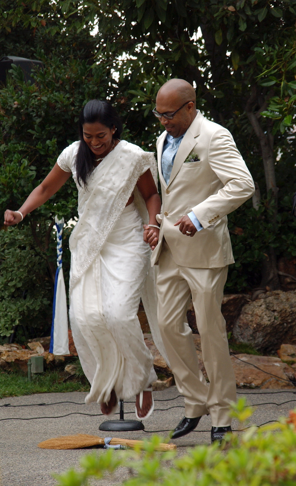 Photo of man and woman couple jumping the broom as part of their wedding ceremony.