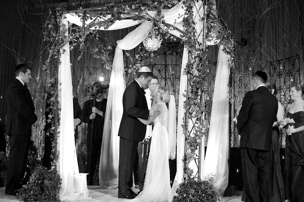 Image of couple celebrating wedding under Chuppah