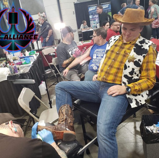 Brian putting an ANDY on the bottom of a boot on a Woody cosplayer