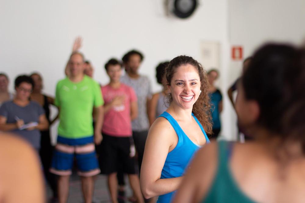 Imagem acessível: Carolina Polezi com camiseta regata azul sorrindo