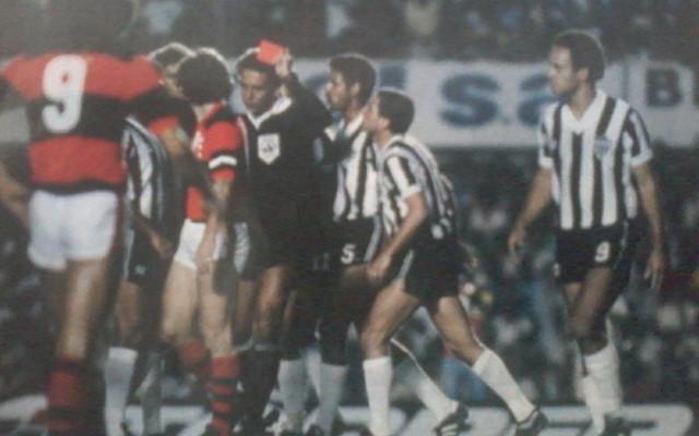 Em campo, o árbitro José Roberto Wright segura um cartão vermelho em uma das mãos, expulsando mais um jogador do Atlético Mineiro. Ele está rodeado por jogadores do Flamengo e do Atlético Mineiro.