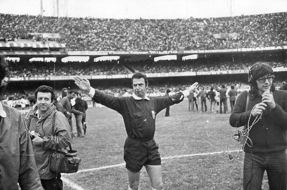 A imagem mostra o árbitro Armando Marques com os braços abertos no campo de futebol encerrando a partida. Ao lado aparecem dois repórteres e ao fundo a torcida nas arquibancadas.