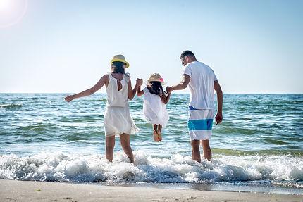 Family of three having fun on tropical b
