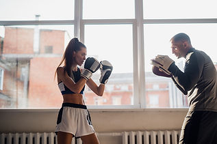 female-boxer-practicing-hits-with-her-pe