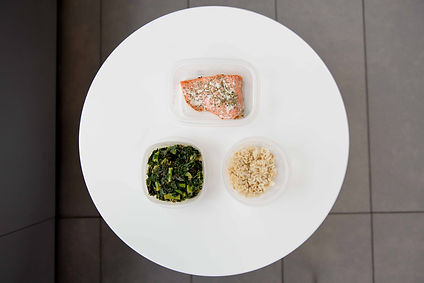 Meal-prepped Tupperware containers of salmon, kale, and brown rice