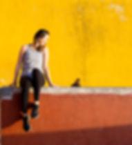 smiling-woman-sitting-on-orange-barrier-