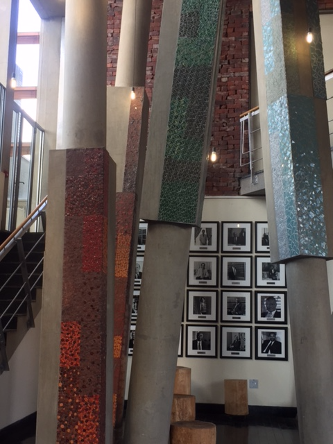 Pillars are covering in different mosaic tiles symbolizing the brown trunks and greens of trees.