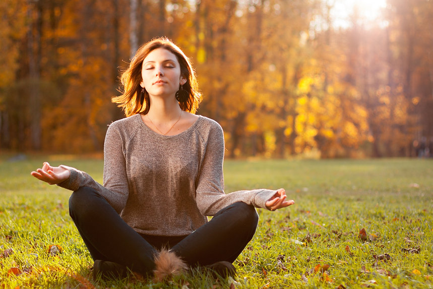 Beautiful young girl meditating in autum