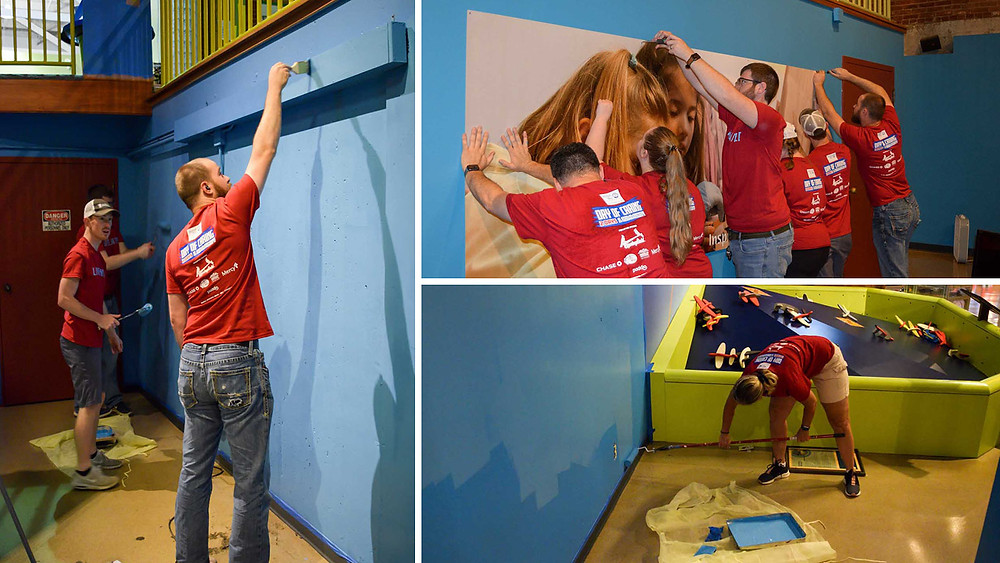 The BRP Architects team works together to re hang up posters on the wall after repainting galleries at the Discovery Center of Springfield
