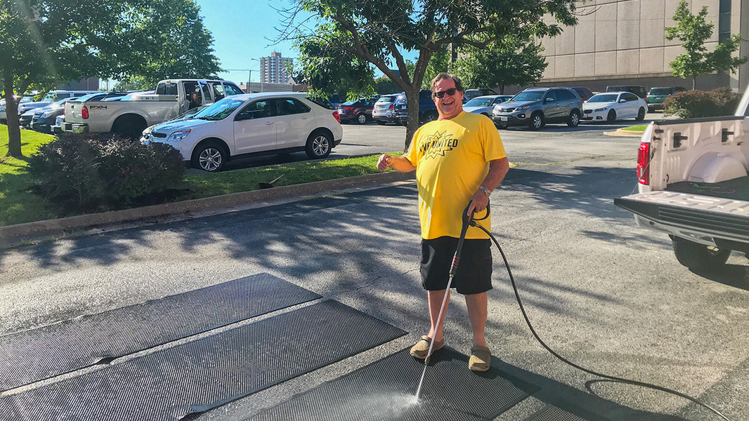 Geoffrey powerwashing floor mats during United Way's Day of Caring