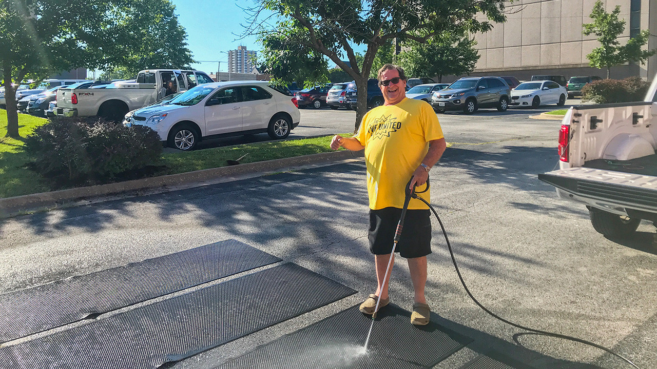 Geoffrey powerwashing floor mats during United Way's Day of Caring