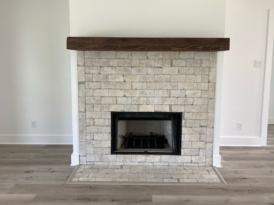 Brick tile fireplace with distressed wood mantle