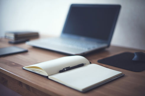 Image of open notebook with pen inside sitting on a desk with open laptop in the background