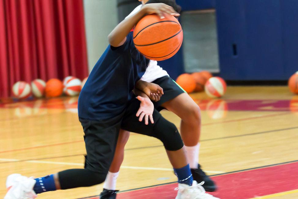 Two teenage male basketball players doin