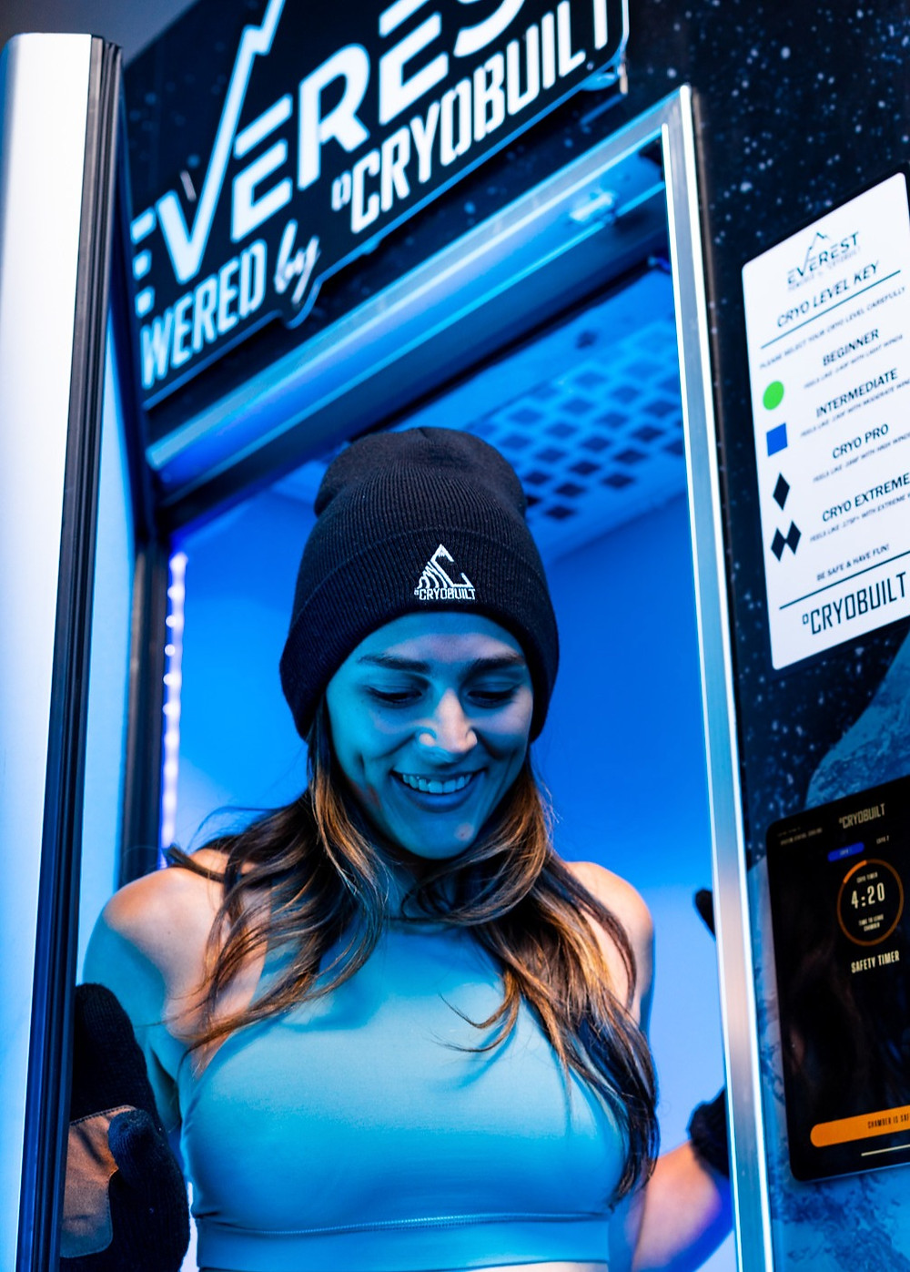 Smiling girl stepping out of Whole Body Cryotherapy chamber