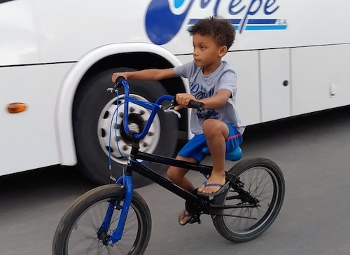 Makai riding his bike next to the Mepe bus
