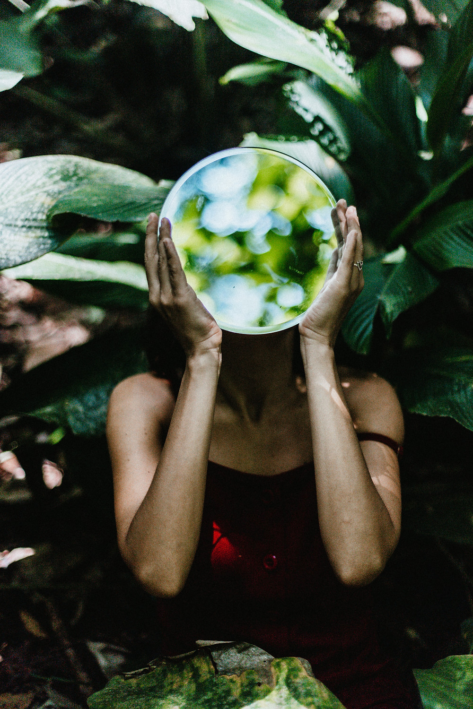mulher na natureza segurando um espelho no rosto e o espelho refletindo a natureza
