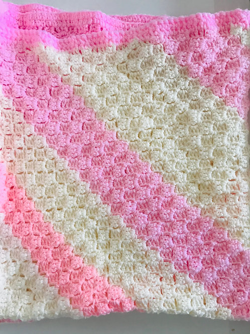 Large knitted pink and cream blanket