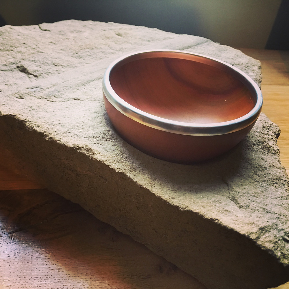 Wild Mango bowl with pewter rim set in Bretton sandstone (with a fossilised tree branch running through it!)