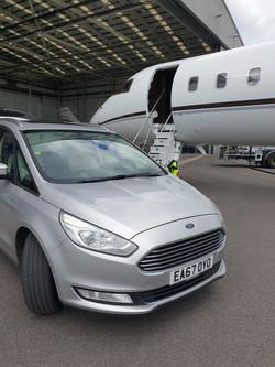 Silver car infont of plane.jpeg