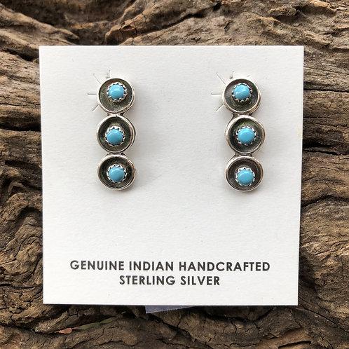 Zuni turquoise snake eyes set into sterling silver bezels.