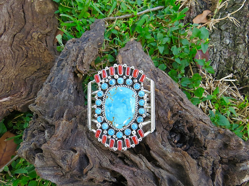 Turquoise cuff with turquoise and coral stones set around single stone, signed